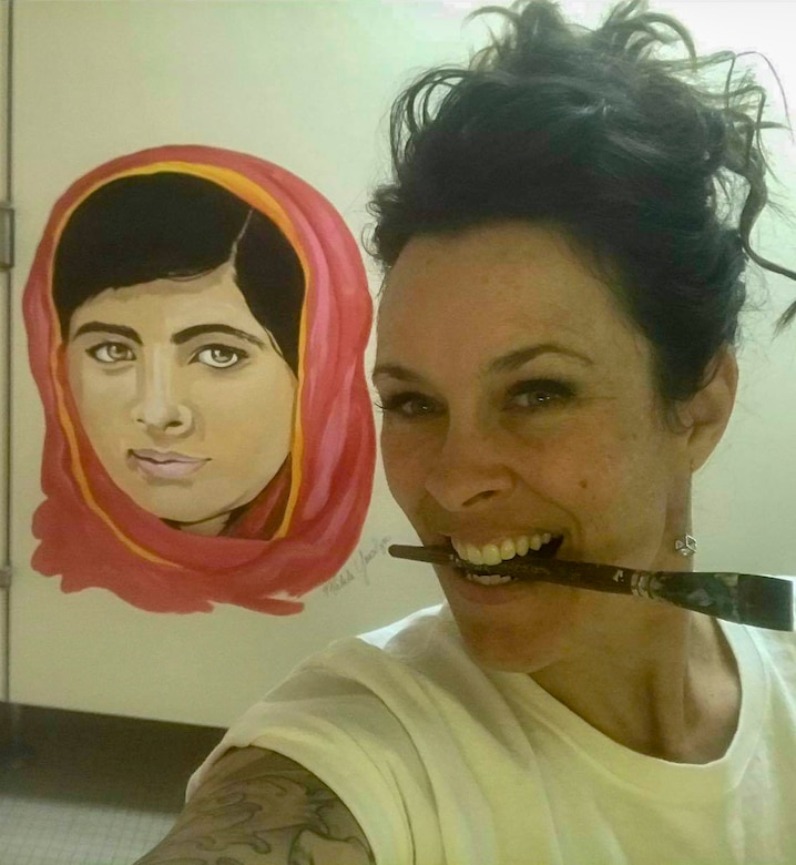 Sharon Smith, the wife of Maj. Brian Smith, a physical therapist with the 35th Medical Operations Squadron, takes a selfie next to her mural in Edgren High School at Misawa Air Base, Japan, in 2018. She creates a culture of positivity and affirmation through her art for the high school students. Smith painted a mural of Malala Yousafzi to inspire young women to stand up for what is right and encourage them to be brave. (Courtesy photo by Sharon Smith)
