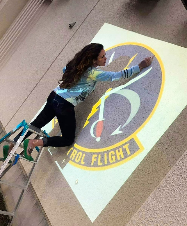 Sharon Smith, the wife of Maj. Brian Smith, a physical therapist with the 35th Medical Operations Squadron, outlines her next mural in the 610th Air Control Flight at Misawa Air Base, Japan, in 2018. She has created 14 murals, which were requested by commanders to boost morale and emphasize the history of the squadrons. (Courtesy photo)