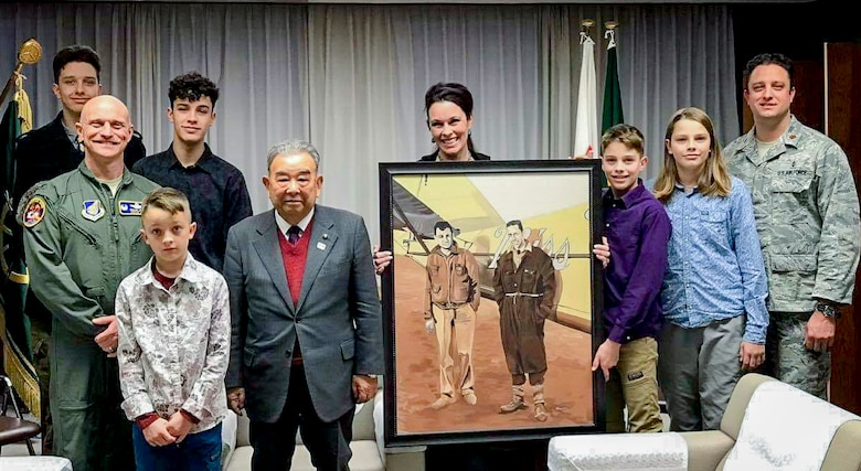 "Sharon Smith, the wife of Maj. Brian Smith, a physical therapist with the 35th Medical Operations Squadron, poses for a photo with Misawa Mayor Kazumasa Taneichi and U.S. Air Force Col. R. Scott Jobe, a former 35th Fighter Wing commander, after the mayor received a photo from Smith at Misawa Air Base, Japan, in 2017. Smith owned the photo from a family relative, which detailed the two pilots of the ""Miss Veedol"" aircraft who made the first Trans-Pacific flight from Japan to the U.S. on Oct. 5, 1931. The gift and piece of history strengthened relations between the U.S. military community and Japan and remains in Misawa City Hall today. (Courtesy photo)"