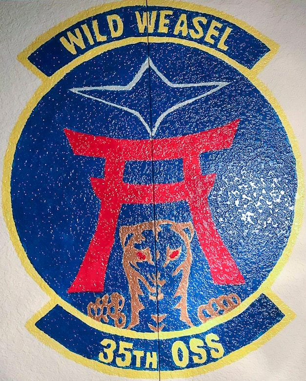 Sharon Smith, the wife of Maj. Brian Smith, a physical therapist with the 35th Medical Operations Squadron, painted the 35th Operations Support Squadron mural at Misawa Air Base, Japan, in 2017. The commander requested her artistic skills to remake the squadron patch into a mural as a way to help create identity and morale in the unit. (Courtesy photo by Sharon Smith)