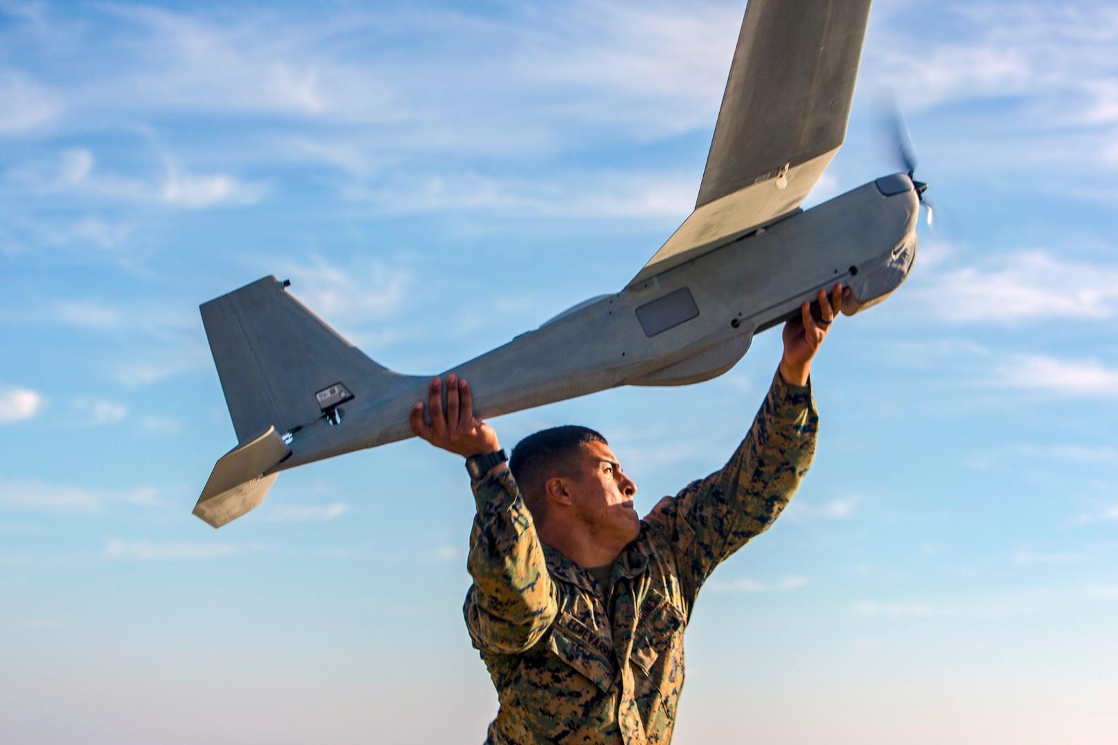 A Marine prepares to throw a drone into flight.
