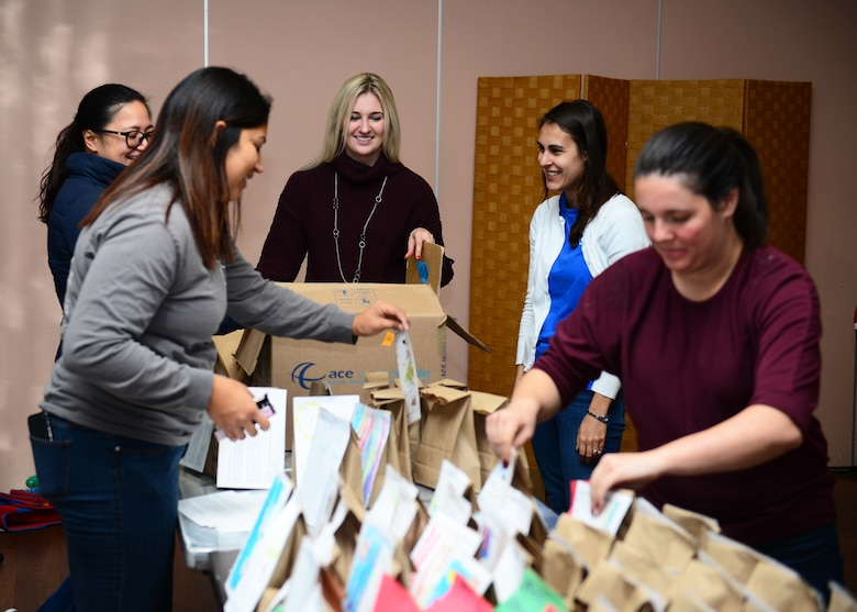 Members of the Spouses of Aviano group work together to attach holiday cards to bags of cookies during the holiday cookie drive at Aviano Air Base, Italy, Dec. 11, 2018. Approximately 25 members of the Spouses of Aviano members volunteered to help at the cookie drive.