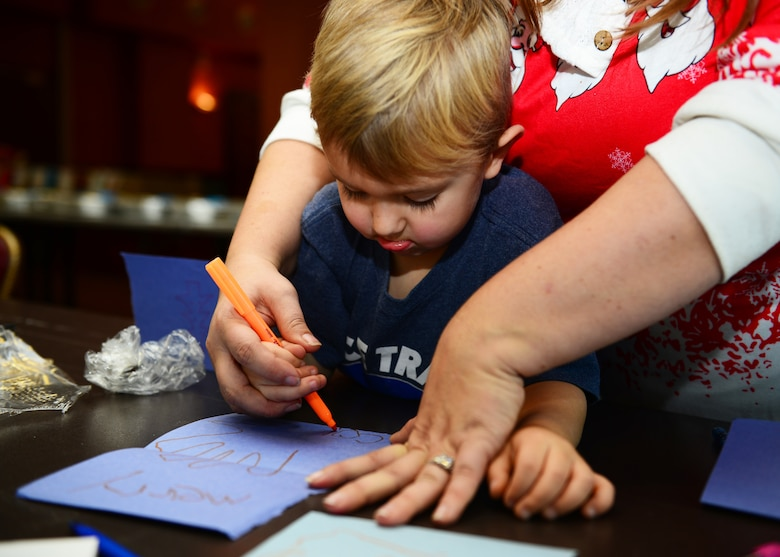 Connor Oden, 4, son of MSgt Michael Oden with the 606th Air Control Squadron, designs a Christmas card during a cookie drive at Aviano Air Base, Italy, Dec. 11, 2018. Connor was assisted by his mother, Rachel Oden, a member of Spouses of Aviano.