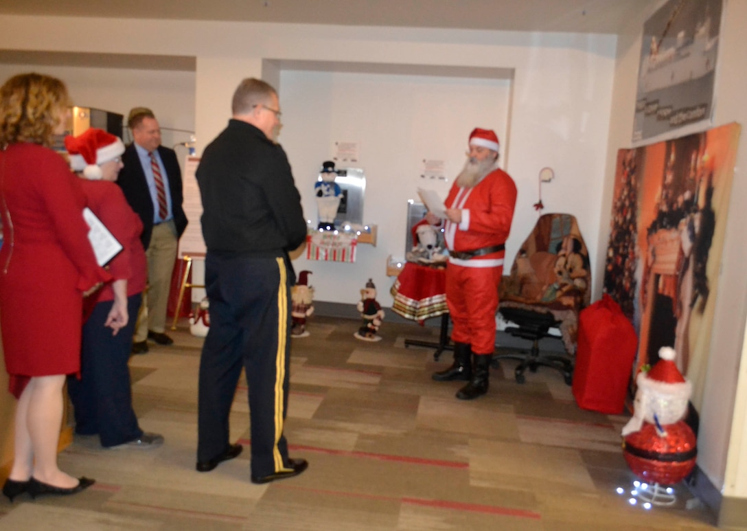 Defense Logistics Agency Troop Support leaders gather as they enjoy a reading from Santa as part of the Medical supply chain's entry in the 2018 holiday decorating contest in Philadelphia Dec. 20, 2018.
