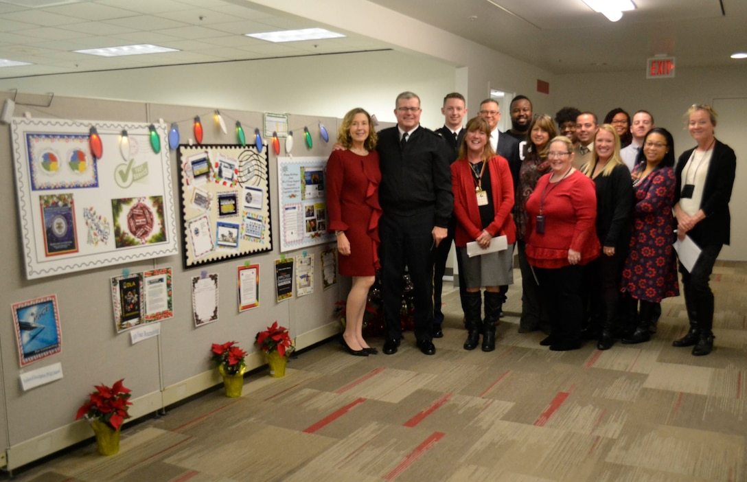 Defense Logistics Agency Troop Support leaders pose with members of the Command Support Office next to their entry in the 2018 holiday decorating contest in Philadelphia Dec. 20, 2018.