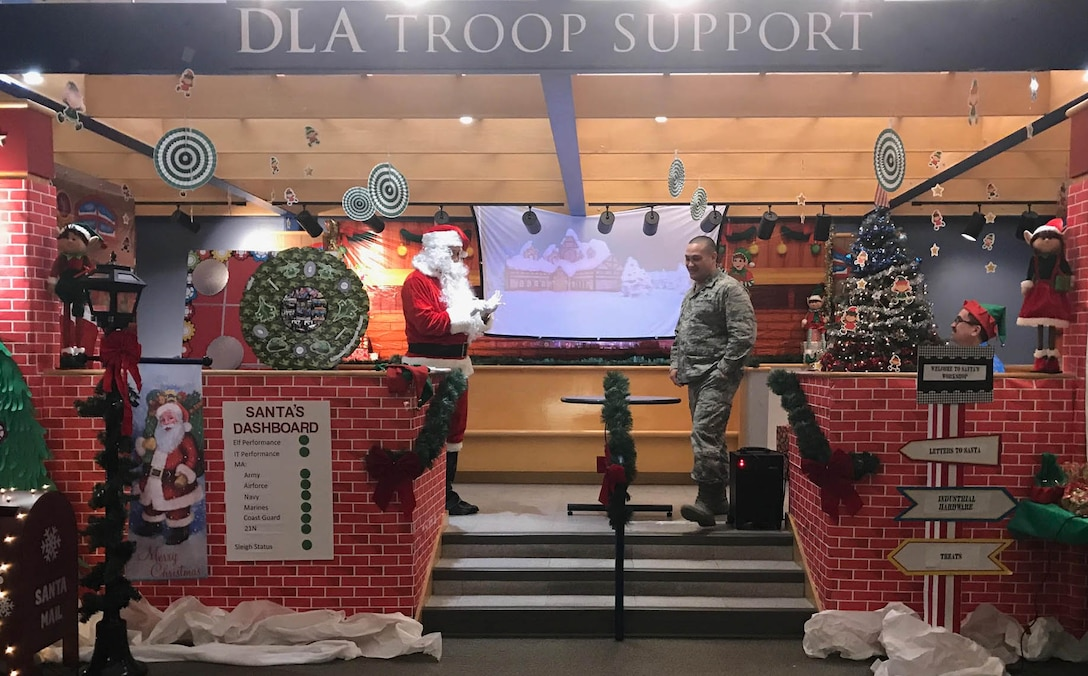 Defense Logistics Agency Troop Support Industrial Hardware Director Air Force Col. Adrian Crowley is addressed by Santa, played by contract specialist Craig Singleton, in a presentation from IH as part of their entry in the 2018 holiday decorating contest in Philadelphia Dec. 20, 2018.