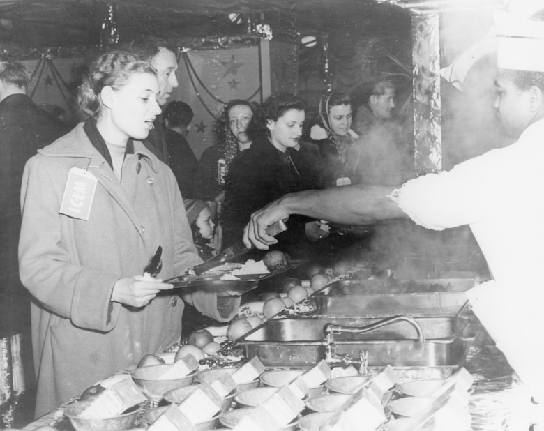A Hungarian refugee, one of 279 who were flown out of Eastern Europe in December of 1956 by C-121s based at Charleston Air Force Base, S.C., receives a meal at the Charleston AFB dining hall.