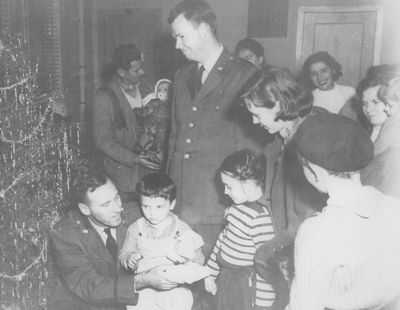 Hungarian refugee children receive Christmas gifts from military and civilian members of Charleston Air Force Base, S.C., in December of 1956.
