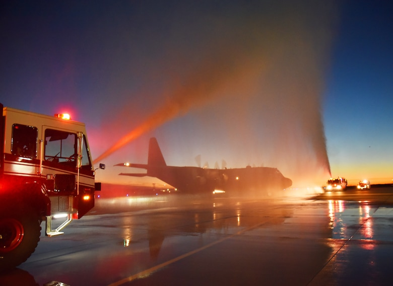 fire trucks spray a C-130H3