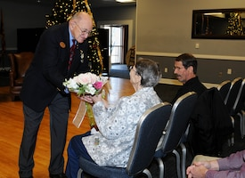 Mark Horning gives flowers to his wife Jean during his retirement Dec 18, 2018, on Columbus Air Force Base, Mississippi. (U.S. Air Force photo by Mary Crump)