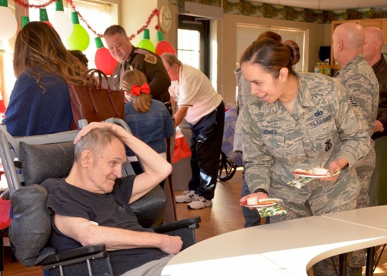 Tech. Sgt. Kathelene Jones, 507th Security Forces Squadron, serves a snack to a veteran Dec. 20, 2018, at the Norman Veterans Center in Norman, Oklahoma. 507th Air Refueling Wing Airmen visited the veterans to deliver gifts and serve snacks for the holidays. (U.S. Air Force photo by Tech. Sgt. Samantha Mathison)