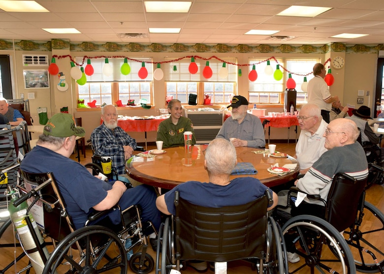Maj. Donna Williams, 465th Air Refueling Squadron KC-135R pilot, visits with a group of veterans at the Norman Veterans Center Dec. 20, 2018, in Norman, Oklahoma. 507th Air Refueling Wing Airmen visited the veterans to deliver gifts and serve snacks for the holidays. (U.S. Air Force photo by Tech. Sgt. Samantha Mathison)