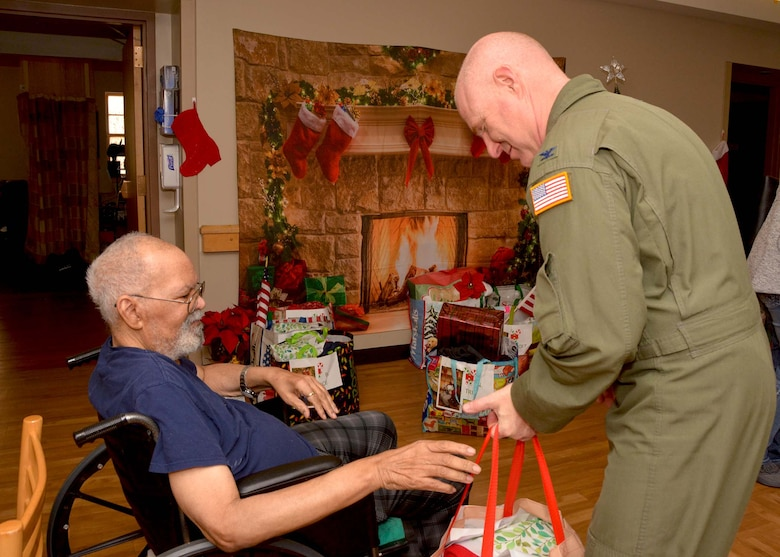 507th Air Refueling Wing Commander, Col. Miles Heaslip, helps a veteran open his gift Dec. 20, 2018, at the Norman Veterans Center in Norman, Oklahoma. 507th ARW Airmen visited the veterans to deliver gifts and serve snacks for the holidays. (U.S. Air Force photo by Tech. Sgt. Samantha Mathison)