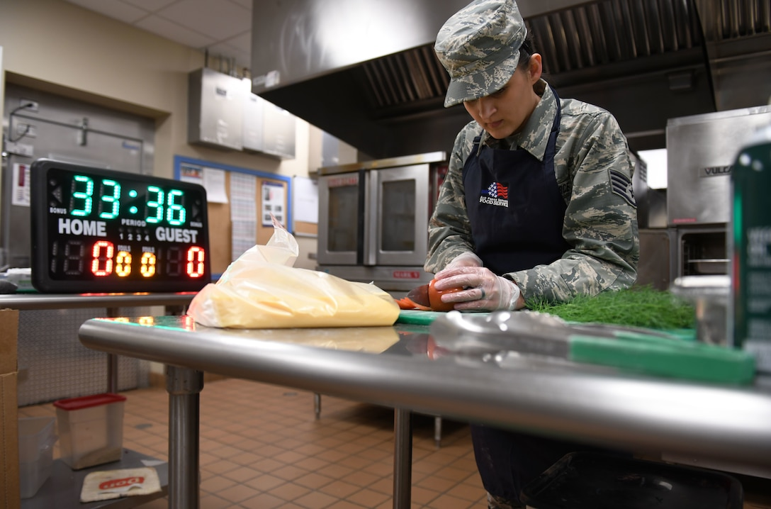 Staff Sgt. Erica Restemayer, a 28th Force Support Squadron noncommissioned officer in charge of retentions and promotions, races against the clock during the Chef of the Quarter cook-off competition at the Raider Café on Ellsworth Air Force Base, S.D., Dec. 18, 2018. Contestants were split into three teams that included one food service Airman and one volunteer NCO. (U.S. Air Force photo by Airman 1st Class Christina Bennett)