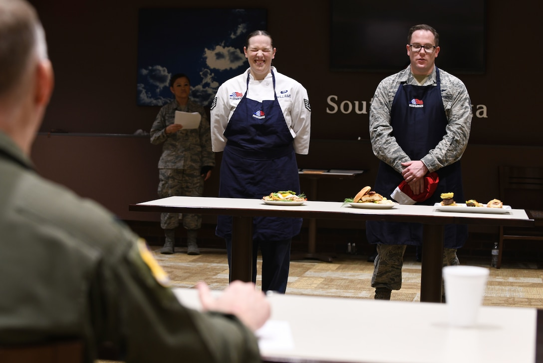 "Staff Sgt. Amanda Williams, a 28th Force Support Squadron food service specialist, stands alongside her teammate, Staff Sgt. Kyle Miesbauer, a 28th FSS unit training manager, at the Chef of the Quarter cook-off competition at the Raider Café on Ellsworth Air Force Base, S.D., Dec. 18, 2018. Judges agreed that all the dishes were delicious and well-prepared, but overall Williams won the competition and was named ""Chef of the Quarter."" (U.S. Air Force photo by Airman 1st Class Christina Bennett)"