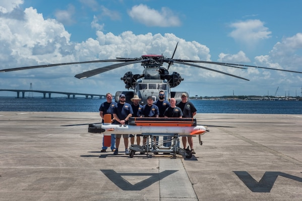 The AN/AQS-24C Mine Detecting Set Airborne Mine Countermeasures In-Service Engineering Activity test team posed for a photo at the conclusion of a successful test event in Panama City, Florida. Pictured from left to right are: Mark Gibbons, Naval Surface Warfare Center Panama City Division (NSWC PCD), Jason Niemczura (NSWC PCD), Kelly Williams (NSWC PCD), Corey Fife (NSWC PCD), Justin Grimes (NSWC PCD), Brett Thach (NSWC PCD), and Gregg Volpe (Northrop Grumman). U.S. Navy photo by Anthony Powers.