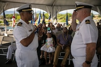 U.S. Navy Lt. Cmdr. Phillip Ridley, Marine Corps Base Hawaii chaplain, receives a retirement flag from Lt. Cmdr. Buster Williams, Marine Aircraft Group 24 chaplain, during Ridley's retirement ceremony on the USS Missouri, Pearl Harbor, Dec. 20, 2018. Ridley retired after 29 years of faithful service to the U.S. Navy. (U.S. Marine Corps photo by Sgt. Zachary Orr)