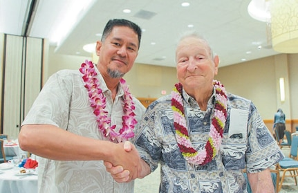 Lewis Walters (right), son of George S.B. Walters, congratulates Dale Hoxie, an electrician supervisor of PHNSY/IMF.