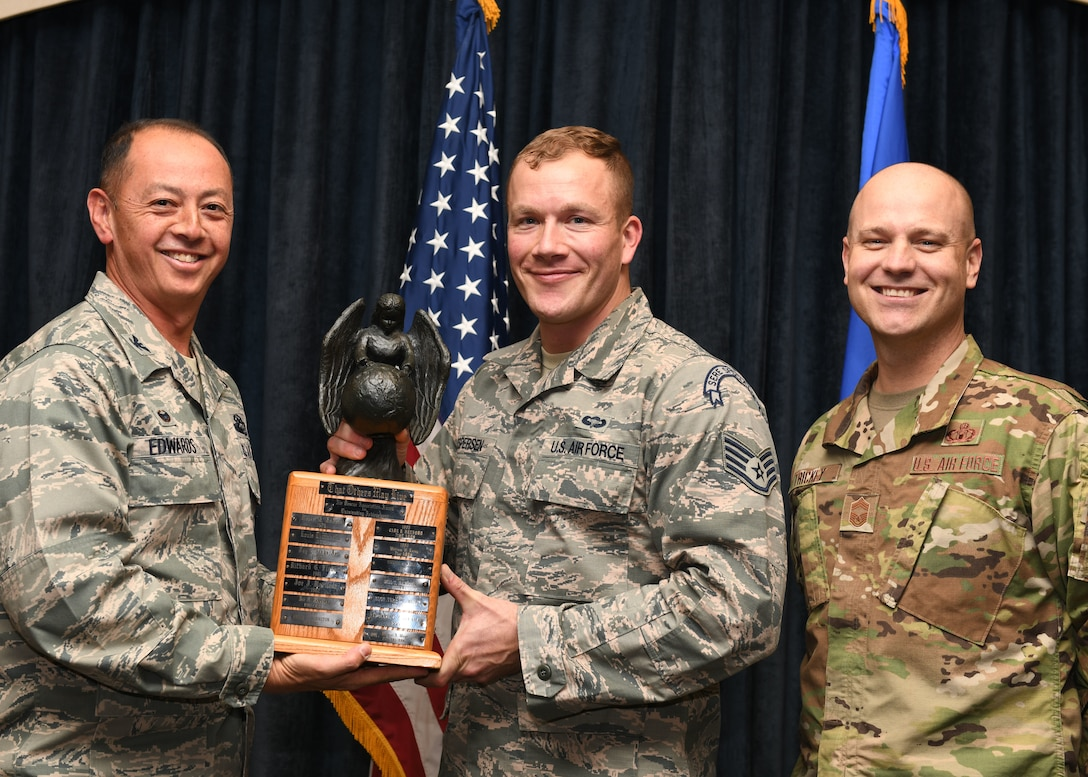 Col. John Edwards and Chief Master Sgt. Jason Trickey present Staff Sgt. Dustin Jespersen with the 2018 Air Association Richard T. Kight Award at the Dakota's Club on Ellsworth Air Force Base, S.D., Oct. 31, 2018. Edwards is the 28th Bomb Wing commander; Jespersen is a 28th Operations Squadron survival, evasion, resistance and escape specialist; and Trickey is the 28th Operations Group superintendent. After being awarded the 2018 Air Rescue Association Richard T. Kight Award, Jespersen was promoted to technical sergeant as part of the Stripes for Exceptional Performers (STEP) program. (U.S. Air Force photo by Airman 1st Class Thomas Karol)