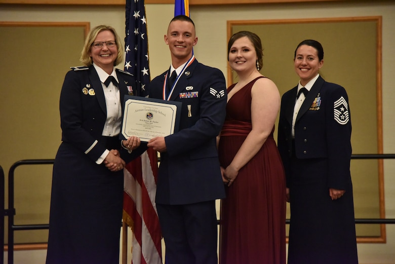 Col. Jennifer Reeves, 341st Missile Wing commander, left, Senior Airman Dylan Taylor, 341st Missile Maintenance Squadron, Mrs. Dylan Taylor and Chief Master Sgt. Eryn McElroy, 341st MW command chief, pose for a photo Dec. 19, 2018, at Malmstrom Air Force Base, Mont. Dylan received the 341st Force Support Squadron Airman Leadership School Class 19-B John L. Levitow Award. (U.S. Air Force by Senior Airman Magen M. Reeves)