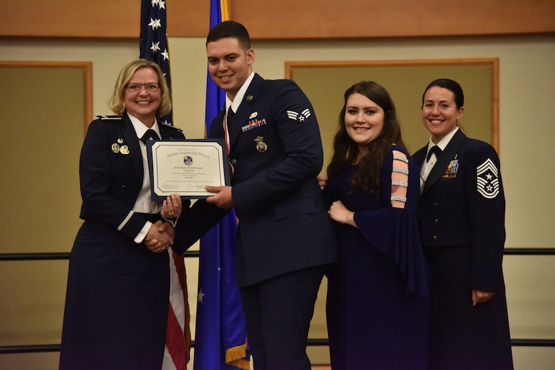 Col. Jennifer Reeves, 341st Missile Wing commander, left, Senior Airman Juan Feliciano, 341st Missile Security Forces Squadron, Mrs. Juan Feliciano and Chief Master Sgt. Eryn McElroy, 341st MW command chief, pose for a photo Dec. 19, 2018, at Malmstrom Air Force Base, Mont. Juan received a 341st Force Support Squadron Airman Leadership School Class 19-B Distinguished Graduate Award. (U.S. Air Force by Senior Airman Magen M. Reeves)