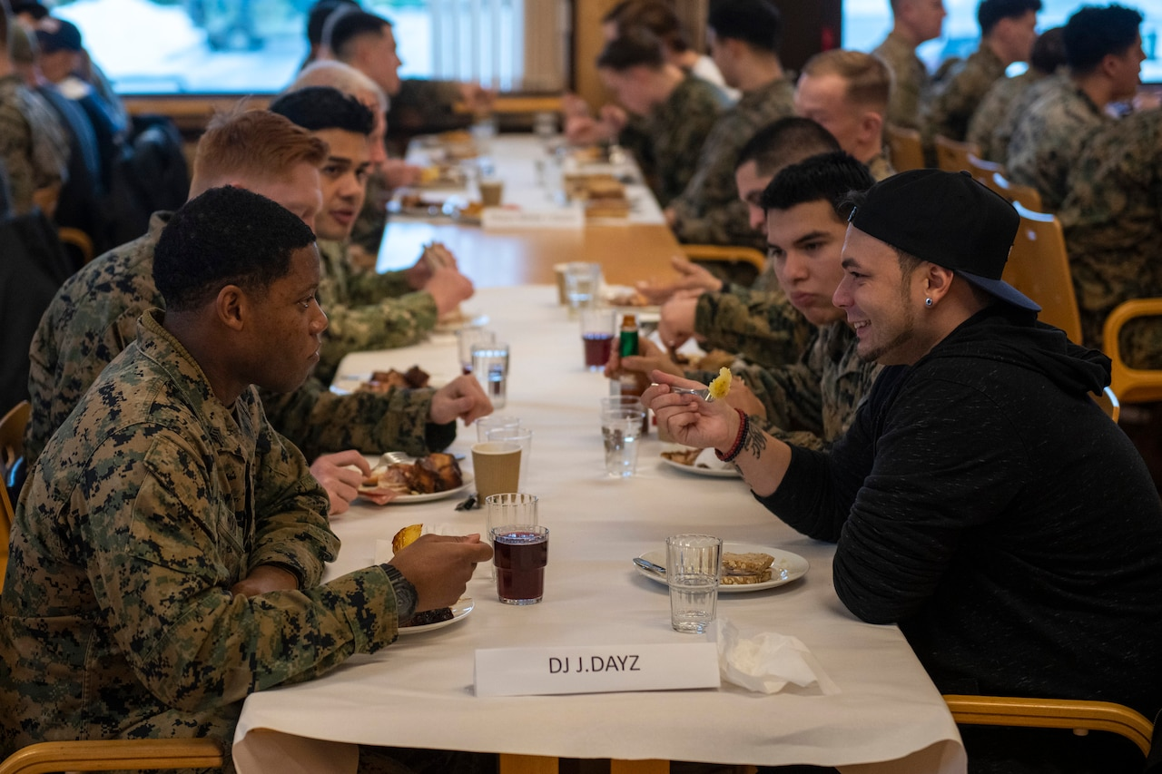 DJ J.Dayz sits and eats with troops in a dining hall.