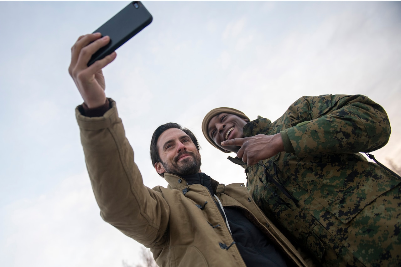 Milo Ventimiglia holds up a phone and poses for a selfie with a smiling service member.