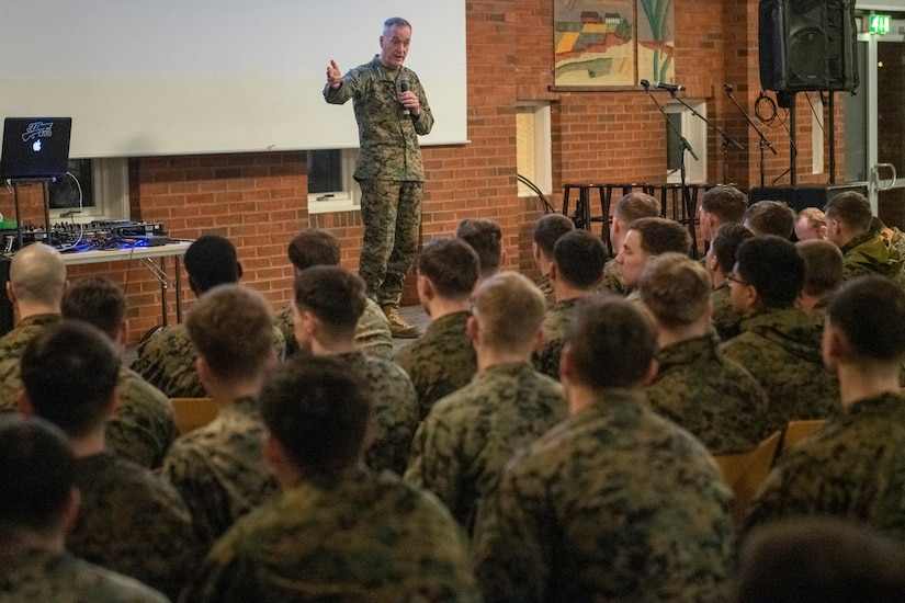 Marine Corps Gen. Joe Dunford talks on a stage to an audience of troops.