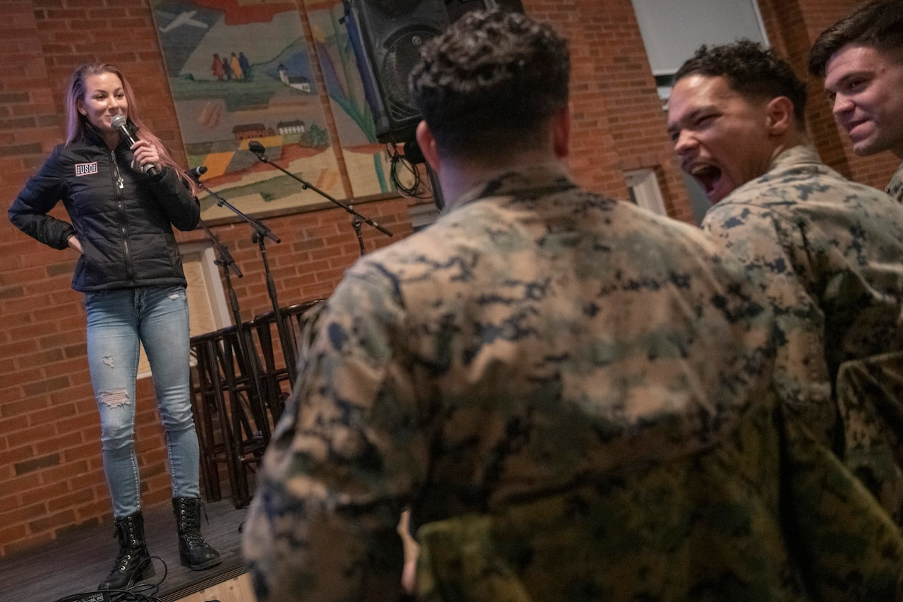 Troops laugh as Comedian Jessiemae Peluso performs on a stage.