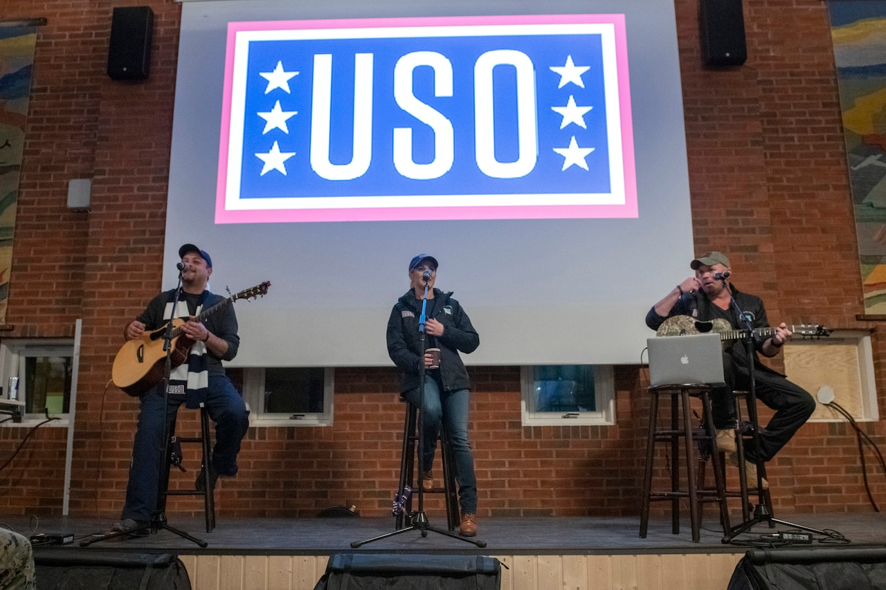 Kellie Pickler performs on a stage with a USO logo in the background.