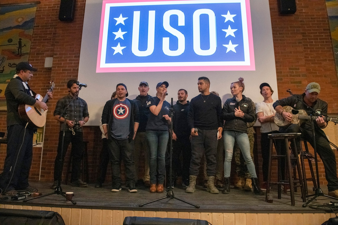 Performers sing on a stage with a USO logo in the background.