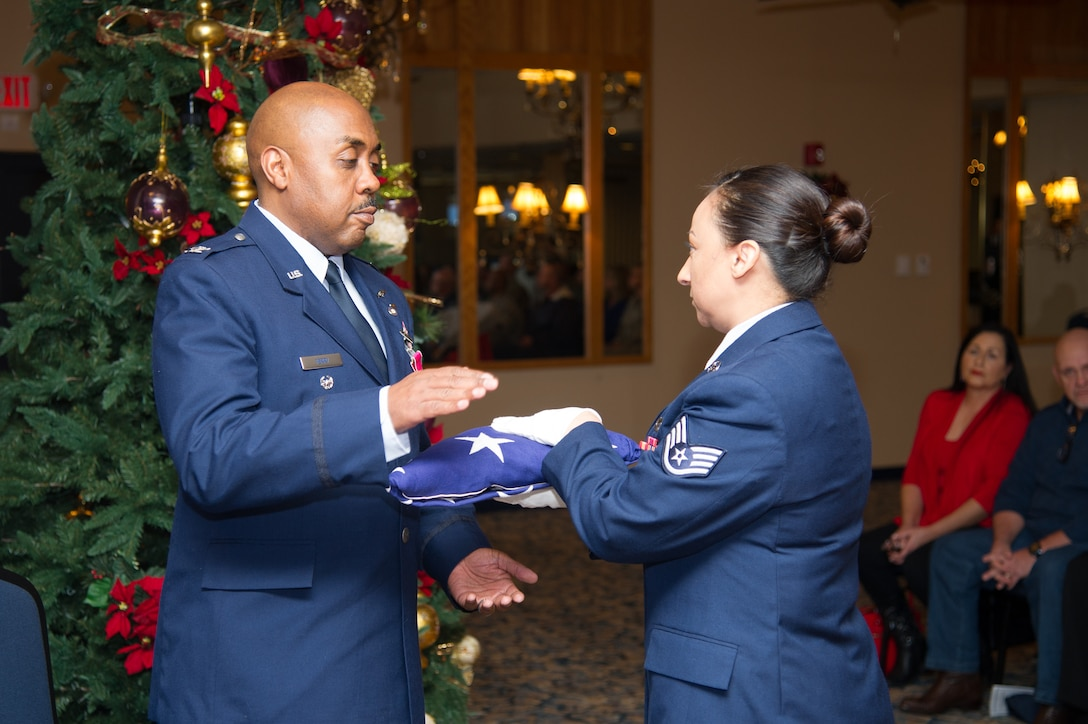 Col. Lloyd Terry is presented with an American Flag by Staff Sgt. Michelle Vallejo during his retirement ceremony, Friday, December 14, at Naval Air Station Fort Worth Joint Reserve Base, Texas, culminating a 35 year career.