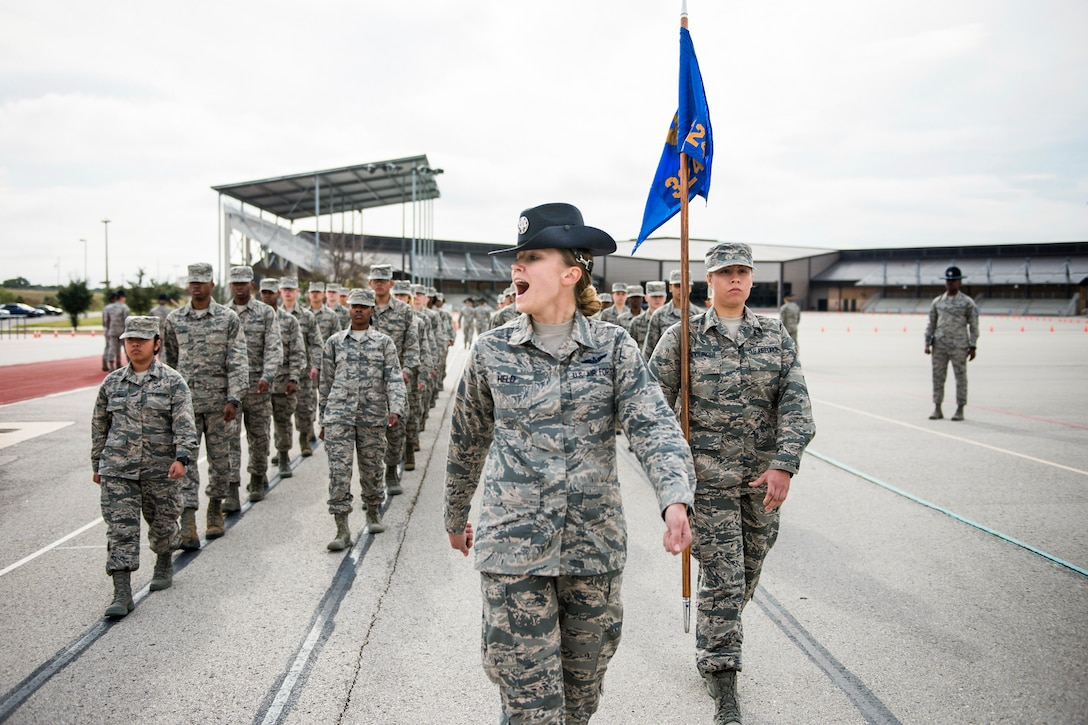 An instructor yells while leading a formation of troops.