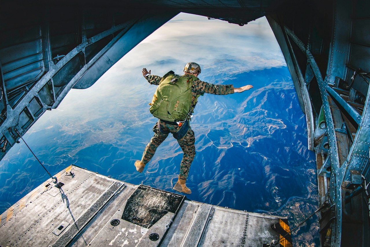 A Marine jumps out of the back of an helicopter flying over mountains.
