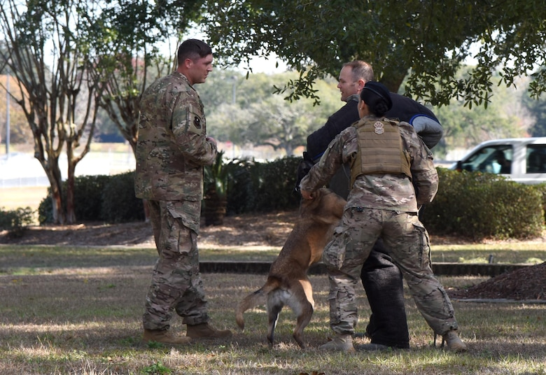 U.S. Air Force Staff Sgt. William Herron, left, 81st Security Forces Squadron military working dog kennel master, Senior Airman Tilar Robinson, 81st SFS military working dog handler, and Maj. Matthew Roberts, 81st Logistics Readiness Squadron commander, participate in a military working dog demonstration during the 81st SFS Day In The Life Of A Defender event at Keesler Air Force Base, Mississippi, Dec. 18, 2018. The event, which was the kick-off for the Year Of The Defender, allowed the 81st SFS to showcase their training and mission capabilities to Keesler leadership. (U.S. Air Force photo by Kemberly Groue)