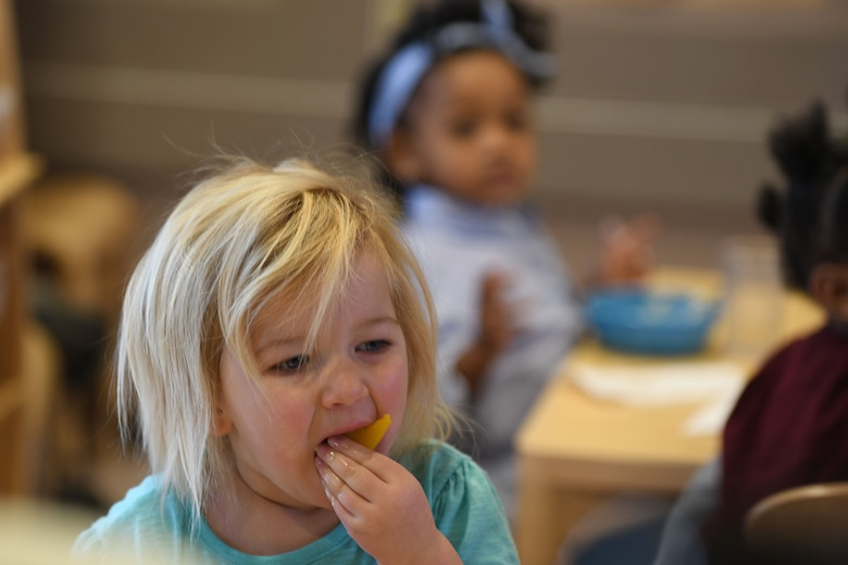 Jaidyn Mastalski, the daughter of 1st Lt. Michael Mastalski, a 28th Maintenance Squadron avionics officer, eats peaches and yogurt during snack time at the McRaven Child Development Center on Ellsworth Air Force Base, S.D., Dec. 6, 2018. The children at the CDC are provided with a nutritious breakfast, lunch and snacks throughout the day. (U.S. Air Force photo by Airman 1st Class Christina Bennett)