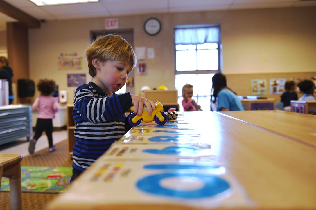 Fox Brookins, the son of Capt. Ryan K. Brookins, the 34th Bomb Squadron assistant director of operations, plays during open playtime in room 138 at the McRaven Child Development Center on Ellsworth Air Force Base, S.D., Dec. 6, 2018. Open playtime gives children a chance to play creatively while developing their motor skills and hand-eye coordination. (U.S. Air Force photo by Airman 1st Class Christina Bennett)