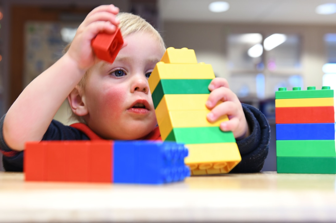 Jackson Scott, the son of Staff Sgt. Matthew Scott a 372nd Training Squadron professional military education instructor, creates a block tower at the McRaven Child Development Center on Ellsworth Air Force Base, S.D., Dec. 6, 2018. Playing with building blocks promotes hand-eye coordination, motor skills and color recognition in young children. (U.S. Air Force photo by Airman 1st Class Christina Bennett)