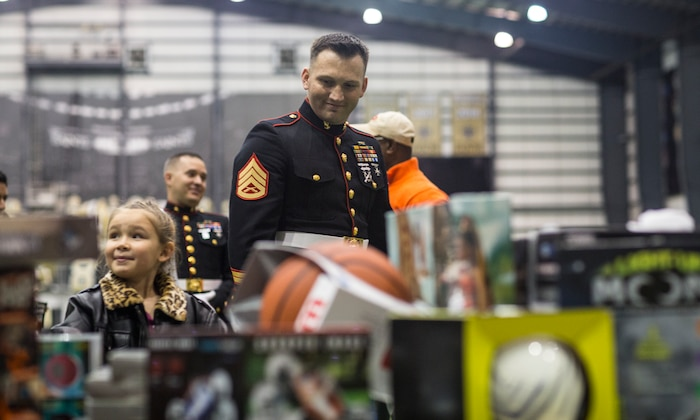Staff Sgt. Mario Acevedo, a training chief with G-3/5, Force Headquarters Group, Marine Forces Reserve, helps a child pick out a toy during a Toys for Tots event at the New Orleans Saints Training Facility in Metairie, La., Dec. 20, 2018.