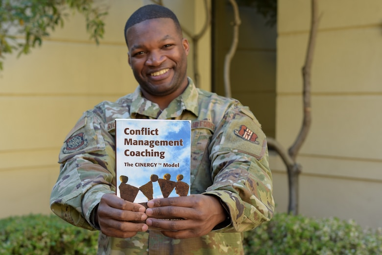 U.S. Air Force Tech. Sgt. Piankhy Richberg, 60th Air Mobility Wing Equal Opportunity NCO in charge, holds a conflict management coaching book Dec. 17, 2018, at Travis Air Force Base, California. The EO office implemented conflict management coaching in June 2018. Since the program's inception, 11 people have used the program. (U.S. Air Force photo by Tech. Sgt. James Hodgman)