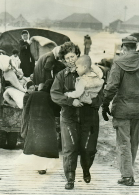 U.S. Air Force Capt. Tone Nobile, a flight nurse, comforts a tiny war victim aboard a Far East Air Forces 315th Air Division transport, during Operation Christmas Kidlift, the evacuation of almost 1,000 orphans from Seoul to safety in South Korea. (U.S. Air Force Photo)