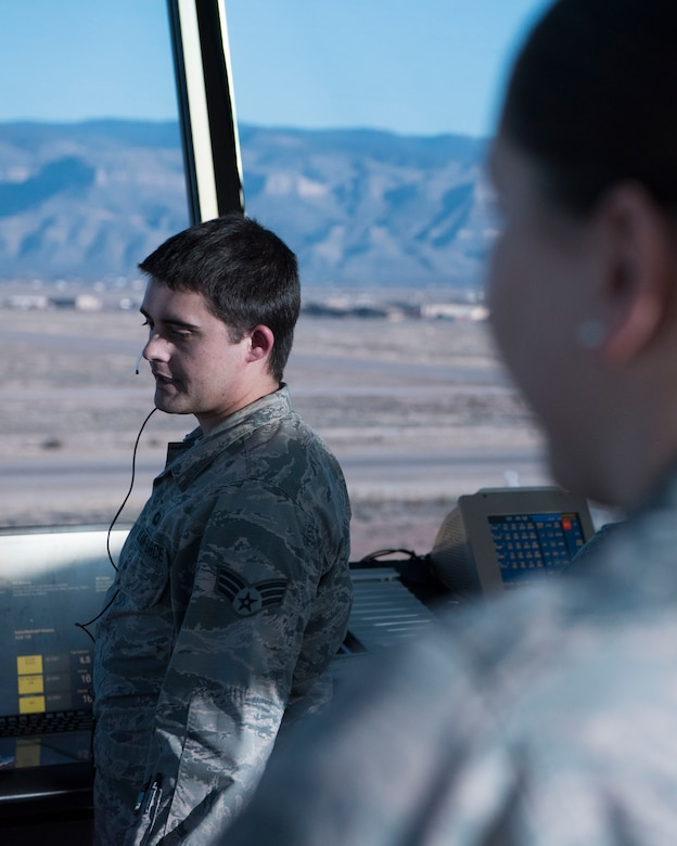 (From left to right) Senior Airman Jakob Powers, 54th Operations Support Squadron air traffic controller, gives a traffic call while being observed by Staff Sgt. Kristin Owens, 54th OSS watch supervisor, Dec. 18, on Holloman Air Force Base, N.M. Holloman is home to one of the most complex airfields in the Air Force because all three of the runways intersect in the shape of the number four (U.S. Air Force photo by Staff Sgt. BreeAnn Sachs)