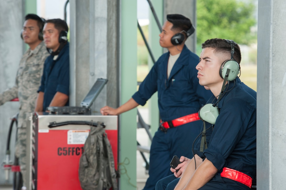 Active duty and Hawaii Air National Guard crew chiefs observe flightline operations after prepping an F-22 Raptor for flight Dec. 10, 2018