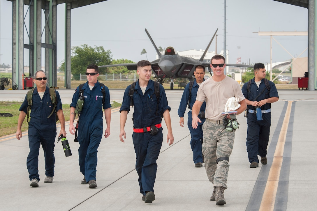 Active duty and Hawaii Air National Guard crew chiefs depart the Joint Base Pearl Harbor-Hickam flightline after prepping F-22 Raptors for flight Dec. 10, 2018