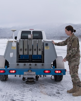 U.S. Air Force Master Sgt. Jill Reed, Air Force Civil Engineer Center's Airfield Pavement Evaluation Team superintendent, checks a special heavy falling weight Dynatest deflectometer, during an evaluation of Bryant Army Airfield at Joint Base Elmendorf-Richardson, Alaska Dec. 17, 2018.  A two-person team used non-destructive testing to assess potential non-visible pavement damage at all of JBER's airfields following the Nov. 30, 7.0 magnitude earthquake, whose epicenter was located just north of the base. The deflectometer simulates 55,000 pounds of weight hitting the pavement at once. (U.S. Air Force photo by Airman 1st Class Crystal A. Jenkins)