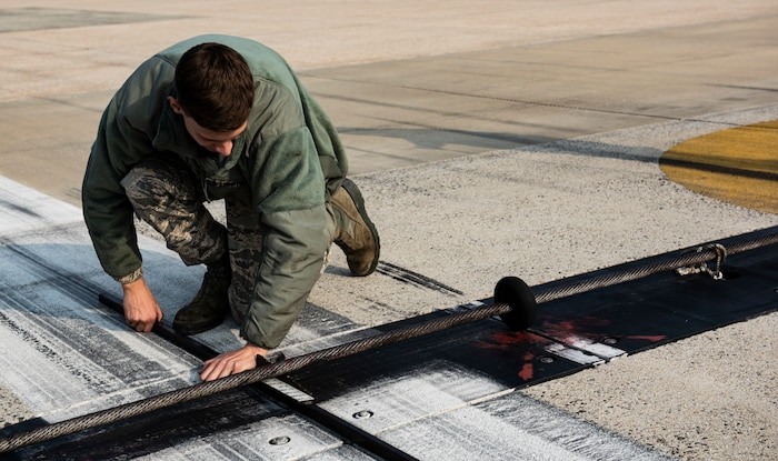 U.S. Air Force Airman 1st Class Zane Mammon, 8th Civil Engineer Squadron electical power production specalis, measures the height of a barrier arresting system at Kunsan Air Base, Republic of Korea, Dec. 19, 2018. The arresting system need to be two inches off the ground to allow enough froom for aircraft to pass over them while still being able to engage it if necessary. (U.S. Air Force photo by Senior Airman Stefan Alvarez)