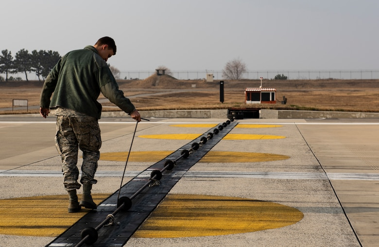 U.S. Air Force Airman 1st Class Zane Mammon, 8th Civil Engineer Squadron electical power production specalist, adjusts a rubber support on a barrier arresting kit at Kunsan Air Base, Republic of Korea, Dec. 19, 2018. Aircraft arresting systems are designed to safely stop an aircraft that's experiencing an in-flight emergency and cannot land without causing damage. (U.S. Air Force photo by Senior Airman Stefan Alvarez)