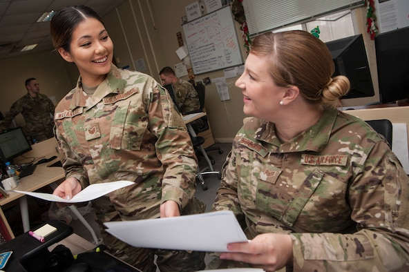 Staff Sgt. Yenshim Watanabe, left, and Staff Sgt. Kristen Rodgers, both 379th Expeditionary Contracting Squadron contingency contracting officers, share contract management best practices Dec. 17, 2018, at Al Udeid Air Base, Qatar. By utilizing their capability to award contracts and procure funding, contracting officers enable a diverse range of projects at Al Udeid including construction, services, commodities and programs. (U.S. Air Force photo by Tech. Sgt. Christopher Hubenthal)