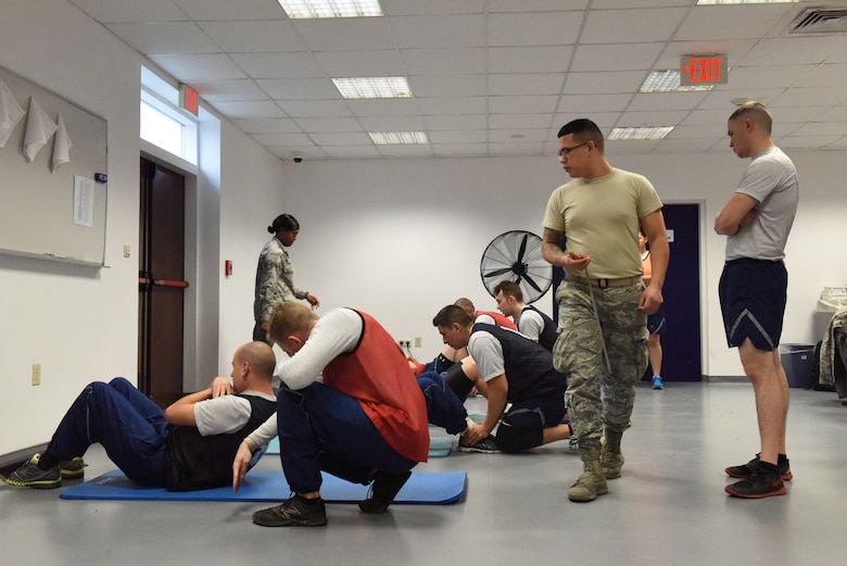 U.S. Air Force Airman 1st Class Jonathan Pena, 39th Force Support Squadron fitness specialist, checks for proper form as service members perform the sit-up portion of their fitness test at Incirlik Air Base, Turkey, Nov. 28, 2018.