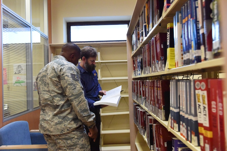 Thomas Lynch, 39th Force Support Squadron supervisory librarian, helps a service member find a book for a college course at Incirlik Air Base, Turkey, Nov. 27, 2018.